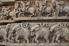 Temple Carvings. Stone carvings of elephants and men on horses on the Hoysala temple at Somnathpur, Karnataka, India stock photography