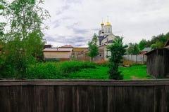 Temple chrétien du dôme et couleur d'or derrière des arbres et des bâtiments privés images libres de droits