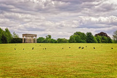 Temple of Concord and rooks in Park of Audley End. Temple of Concord and black rooks in Park of Audley End House in Essex in England. It is a medieval county royalty free stock photos