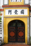 Temple Doors. An entrance to a Chinese temple in Hanoi.  The temples in Hanoi, use a beautiful mustard yellow color and are usually simply decorated Stock Photos