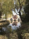 Temple Double Arching Bridges. A red temple in the background with a double arching bridge in the foreground Body of water seen through the branches of a tree stock images