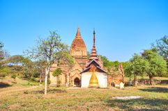 The temple with embedded pagoda in Old Bagan, Myanmar. The small medieval religion complex with gilded stupa embedded into the wall of new temple in Old Bagan Royalty Free Stock Image