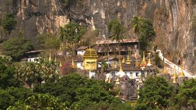 Temple exhibit within trees and cliff. Steady, medium wide shot of a Buddhist temple next to trees and cliffs stock video