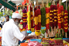 Temple florists prepare flowers and garlands for sale Stock Photos