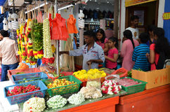 Temple florists prepare flowers and garlands for sale Royalty Free Stock Image