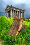 The temple of Garni, the cross. The temple of Garni. In the foreground is a carved stone with Christian symbols in the green grass Royalty Free Stock Images