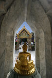 Temple gates. Budda statue in front of gates of a temple in Bangkok, Thailand Stock Photo