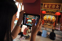 Temple-Goer Uses Tablet To Photo Chinese Shrine. A temple-goer uses a tablet device to capture prayer at a Chinatown shrine on Dec 18, 2013 in Bangkok, Thailand Royalty Free Stock Image