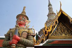 Temple Guardian at Grand Palace in Bangkok. A temple guardian spirit is seen guarding a brightly coloured and ornate temple complex in Bangkok, Thailand with a Stock Photos