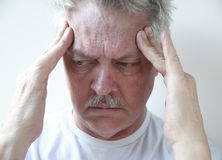 Temple headache in older man. Senior man with fingers on his throbbing headache pain Stock Images