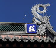 In the temple, housing at the top of a sculpture of a dragon. Dragon in the temple, covered with scales, yawning totem Stock Photography