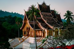 Temple in luang prabang. sky is getting red at sunset. beautiful golden walls. stock image