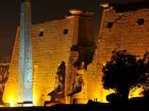 The Temple of Luxor at night. The entrance to the ancient egyptian temple of luxor at night, with giant statues of Ramses II and the great obelisk Stock Photos