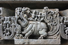 Hoysaleswara Temple outer wall carved with sculpture of Varuna god of rain marching on his Makara mythical animal. This is a Temple outer wall carved with Royalty Free Stock Images