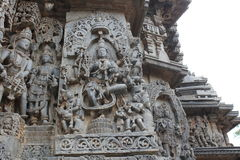 Hoysaleswara Temple outside wall carved with sculpture of goddess lakshmi goddess of wealth and prosperity standing on lotus Stock Photography