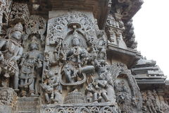 Hoysaleswara Temple outside wall carved with sculpture of goddess lakshmi goddess of wealth and prosperity standing on lotus Stock Photo