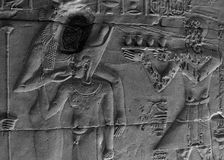 Temple of Phila - bas-relief. Ancient hieroglyphics on the wall in the Temple of Philae at Aswan, Egypt. Damaged bas-relief princess Isis to feed the Horus Stock Photography