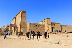 Temple of Philae dedicated to the Goddess Isis. ASWAN, EGYPT - FEBRUARY 1, 2016: Tourists visiting the Graeco-Roman Temple of Philae dedicated to the cult of stock photography