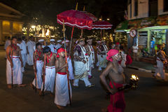 Temple priests and entourage walk along a street in Kandy at the completion of the Esala Perahera in Kandy, Sri Lanka. Stock Photos