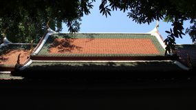 Temple Roof And Leaves. Temple roof cover with colorful tiles and sunlight with blue sky Buddhist temple in Thailand royalty free stock photography