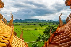 Temple roof green rice field mountain landscape. Temple roof green rice field and mountain landscape stock photo