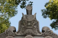Temple Roof Ornament. A face decorates the corner of a temple roof in the city of Fukuoka, Japan stock image