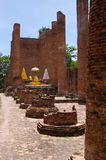 Temple ruin with Buddha in Ayuttaya, Thailand. Interior of temple ruin in the ancient city of Ayuttaya in Thailand, with a golden Buddha with sacred umbrellas Royalty Free Stock Image