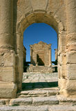 The temple seen via the triumphal arch in Sufetula. Tunisia. Ancient Sufetula (present day Sbeitla). Entrance to the forum via the triumphal arch. View of one Royalty Free Stock Photography