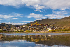 Temple in tibet in blue sky. Temple in Tibet at blue sky at noon, Songzanlin temple, panorama view,with reflection Stock Photo