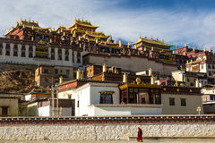 Temple in tibet with a Lama. Temple in Tibet at blue sky at noon, Songzanlin temple, panorama view with Lama Stock Photography