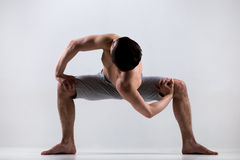 Temple twist yoga pose. Athletic muscular young man working out, yoga, pilates, fitness training, doing sumo squat exercises, revolved temple, goddess, sumo Stock Photos