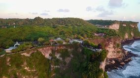 Temple of Uluwatu at sunset. Shooting from the air. Temple on a rock. Beautiful nature, ocean, rock, greenery. Journey. Asia. Indonesia, Bali. Summer stock video