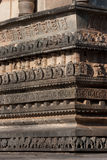 Temple Wall. Intriate carvings on ancient hindu temple wall. Elephants are carved at the base to indicate stability and a solid foundation. Other levels have Royalty Free Stock Photography