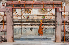 Temple wall with walking monk in yellow buddhist dress Royalty Free Stock Image