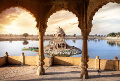 Temple on the water in India. Arches and temple in Gadi Sagar lake at sunset sky in Jaisalmer, Rajasthan, India Royalty Free Stock Images