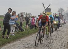 Group of Cyclists - Paris-Roubaix 2018. Templeuve, France - April 08, 2018: Group of cyclists riding on the cobblestone road in Templeuve in front of the Royalty Free Stock Photography