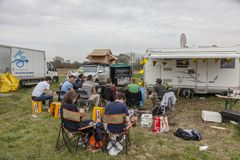 Spectators - Paris-Ropubaix 2018. Templeuve, France - April 08, 2018: Group of spectators outdoors on the roadside watching on a TV the live race broadcast in Royalty Free Stock Photo