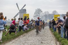 The Peloton - Paris-Roubaix 2018. Templeuve, France - April 08, 2018: The peloton riding on the cobblestone road in Templeuve in front of the traditional Vertain Royalty Free Stock Photo