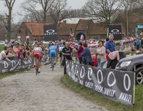 Group of Cyclists - Paris-Roubaix 2018. Templeuve, France - April 08, 2018: Rear view of a group of cyclists riding on the cobblestone road in Templeuve during Royalty Free Stock Photography