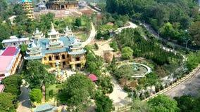 Templo budista del amarillo de la visión general entre jardín tropical almacen de metraje de vídeo