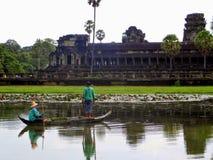 Templo de Angkor Wat durante el día que ofrece una pesca del hombre y de la mujer en un bote pequeño que mira el templo en el fon Foto de archivo libre de regalías