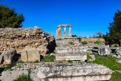 Templo de Apollo em Corinth antigo Grécia visto para baixo do hll nas ruínas escavadas com os turistas unidentifiable que tomam o foto de stock