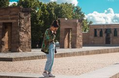 Templo de Debod, Madrid ESPAÑA - 10 DE JUNIO DE 2018 Mujer elegante joven con el peinado casual del bollo que admira el monumento imagen de archivo