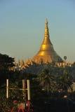 Templo de la pagoda de Shwedagon con el pueblo abajo en la luz de la mañana Imagen de archivo libre de regalías