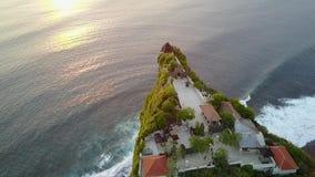 Templo de Uluwatu en la puesta del sol Tiroteo del aire Templo en una roca Naturaleza hermosa, océano, roca, verdor Viaje asia In almacen de video
