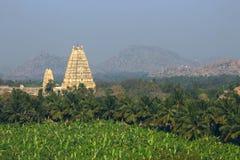Templo de Virupaksha entre las montañas y las plantaciones de la palma en salida del sol Imágenes de archivo libres de regalías