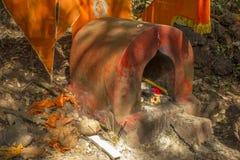 Templo hindu gasto vermelho antigo com bandeiras alaranjadas e ofertas na floresta imagem de stock royalty free