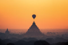 Templos en Bagan con el globo del aire caliente para traval en subida del sol y Fotos de archivo libres de regalías
