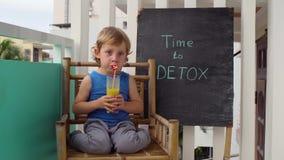TEMPO à inscrição do giz da DESINTOXICAÇÃO O menino é beber fresco, saudável, bebida da desintoxicação feita dos frutos A agitaçã vídeos de arquivo