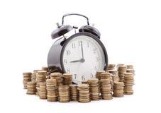 Tempo é dinheiro Despertador com as pilhas de moedas Imagem de Stock Royalty Free